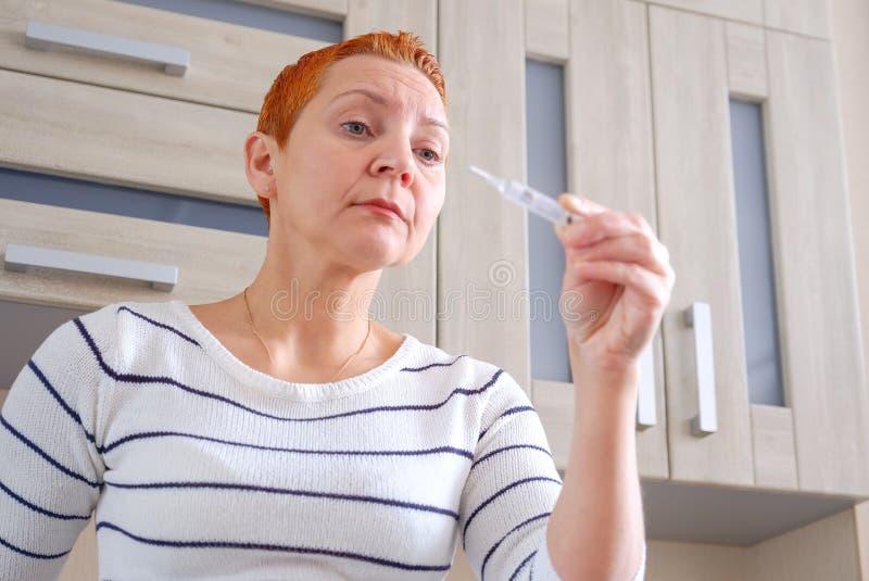 Vrouw met een thermometer in haar hand Opgeheven lichaamstemperatuur royalty-vrije stock afbeelding