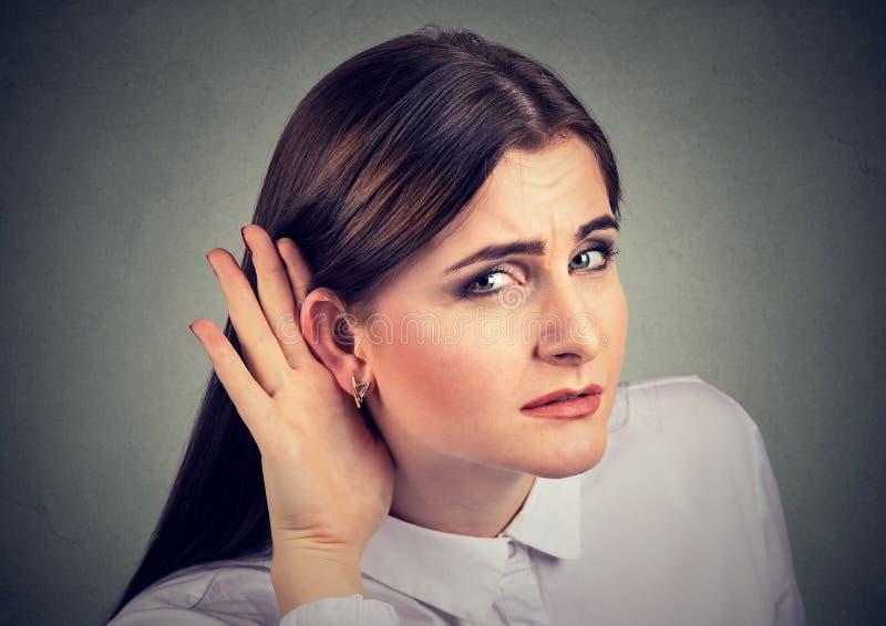 Vrouw met een verlies van het gehoor die haar hand achter oor tot een kom vormen om beschikbaar geluid te proberen en te vergrote stock fotografie