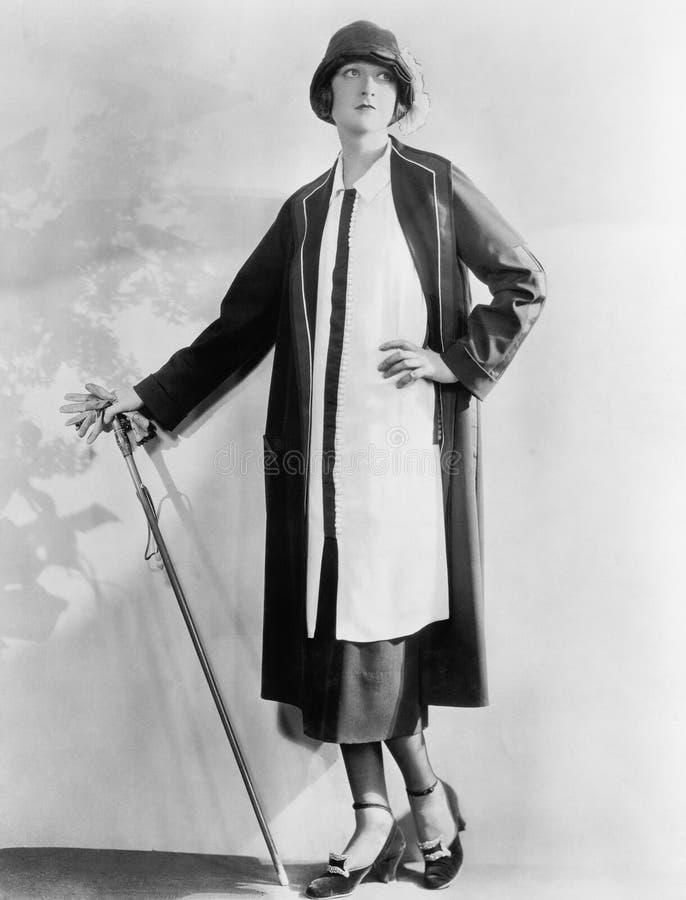 Vrouw met een wandelstok in een elegante kleding en een laag (Alle afgeschilderde personen leven niet langer en geen landgoed bes royalty-vrije stock fotografie