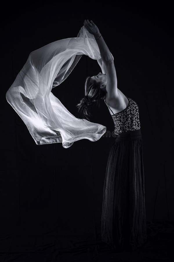 Vrouw met een witte sjaal op een zwarte achtergrond royalty-vrije stock foto