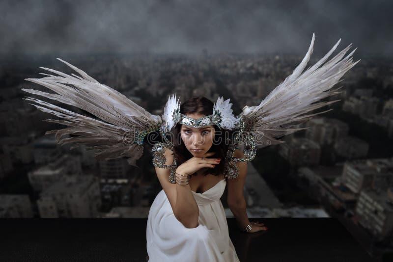 Vrouw met engelenvleugels op de achtergrond van de smoggy stad stock foto's