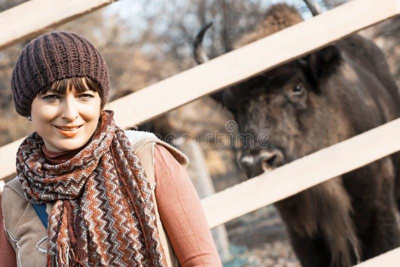 Vrouw met Europese bisonbehind de omheining stock afbeelding