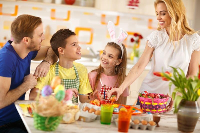 Vrouw met familie die Pasen-mand met eieren voorbereiden royalty-vrije stock foto's