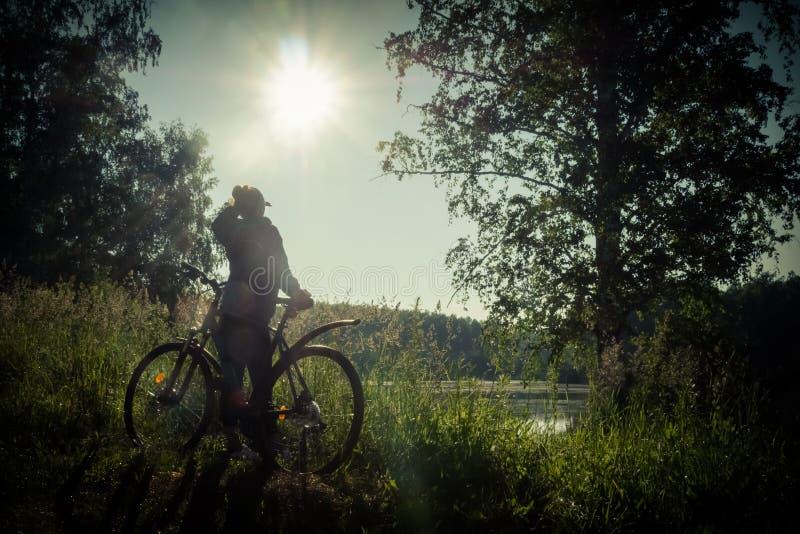 Vrouw met fiets dichtbij het meer royalty-vrije stock foto