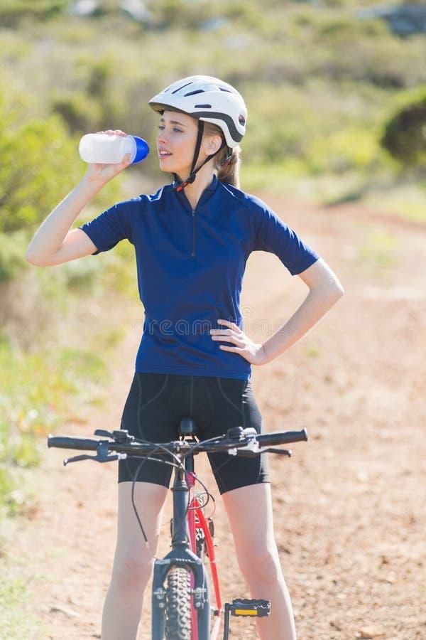 Vrouw met fiets drinkwater stock afbeelding