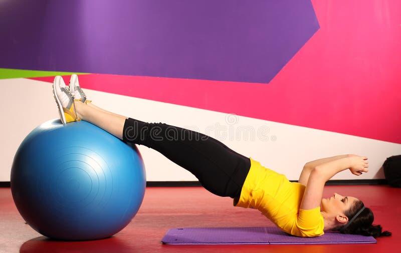 Vrouw met fitness bal in gymnastiek bij fysieke opleiding in sportslijtage royalty-vrije stock afbeeldingen