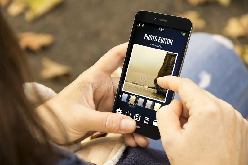 Vrouw met fotoredacteur app in het park stock afbeeldingen