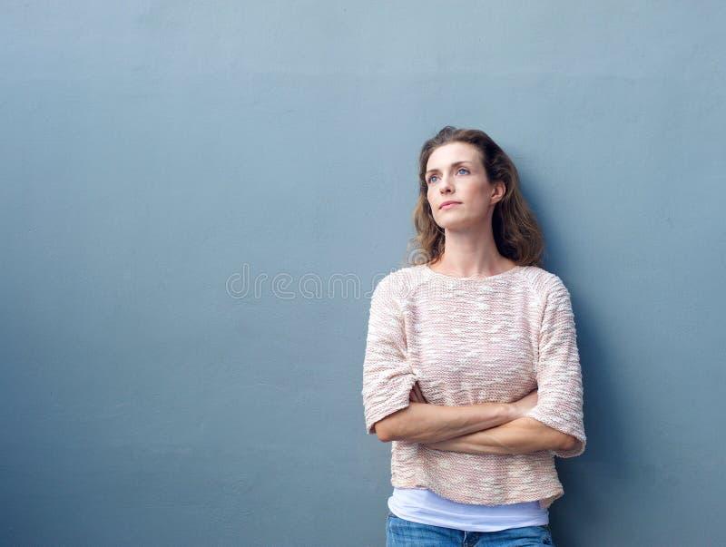 Vrouw met gekruiste wapens het kijken weg met nadenkende uitdrukking royalty-vrije stock afbeeldingen