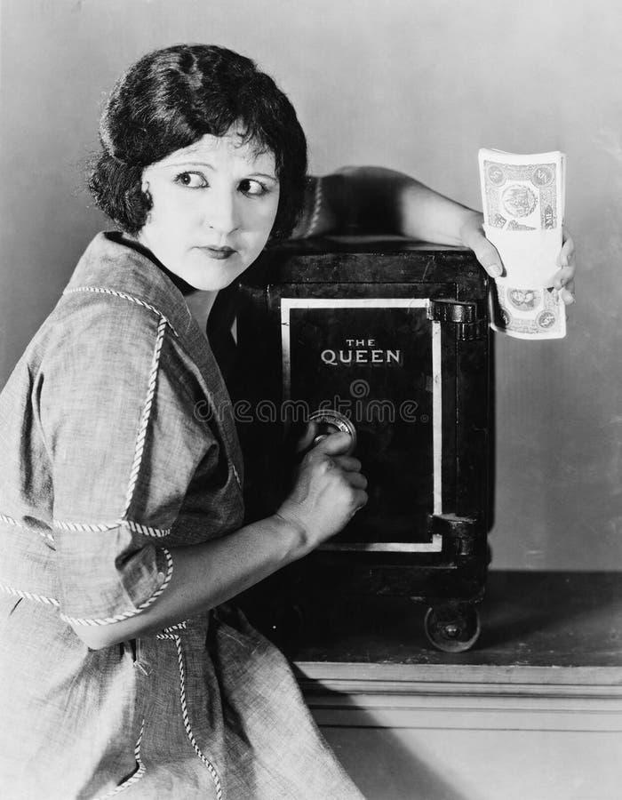 Vrouw met geld en brandkast (Alle afgeschilderde personen leven niet langer en geen landgoed bestaat Leveranciersgaranties die da stock fotografie