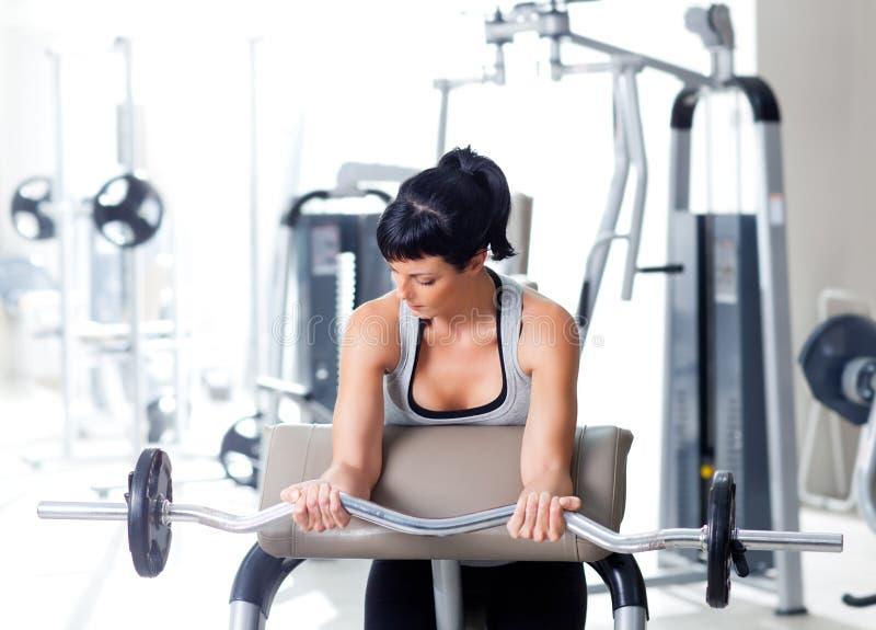 Vrouw met gewichtheffenapparatuur op sportgymnastiek stock foto