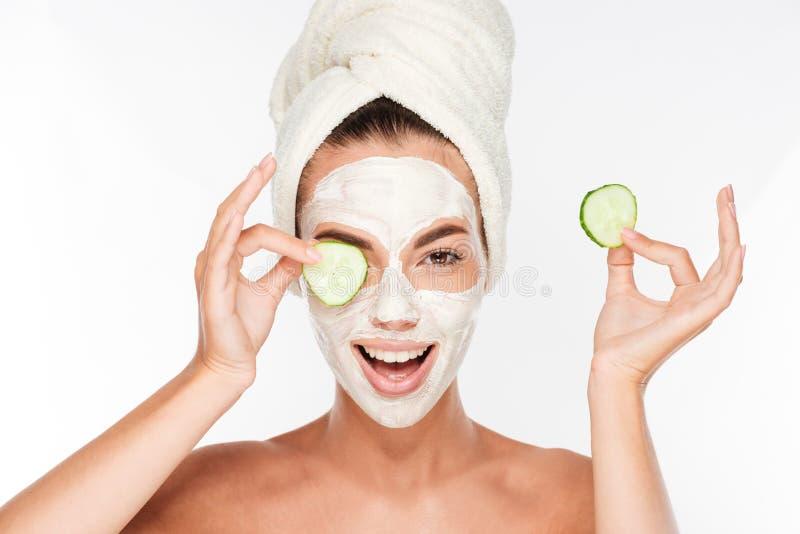 Vrouw met gezichtsmasker en komkommerplakken in haar handen stock afbeeldingen