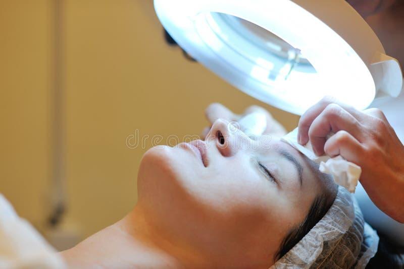 Vrouw met gezichtsmasker in kosmetische studio stock afbeelding
