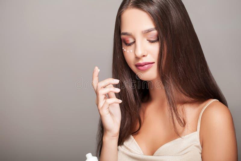 Vrouw met gezond gezicht die kosmetische room toepassen onder de ogen stock foto