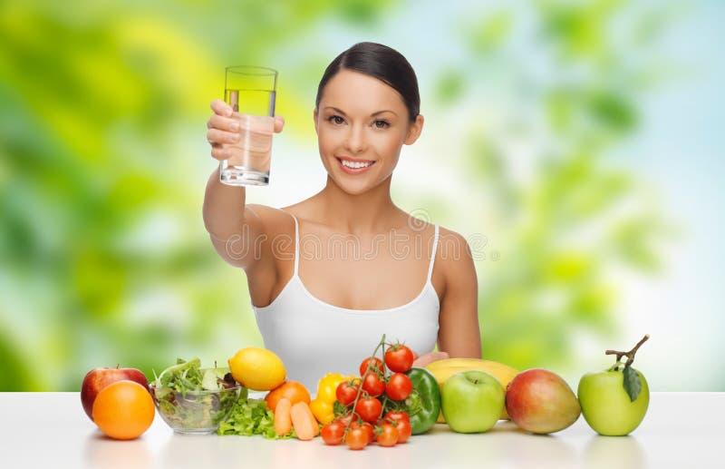 Vrouw met gezond voedsel op lijst drinkwater royalty-vrije stock foto's