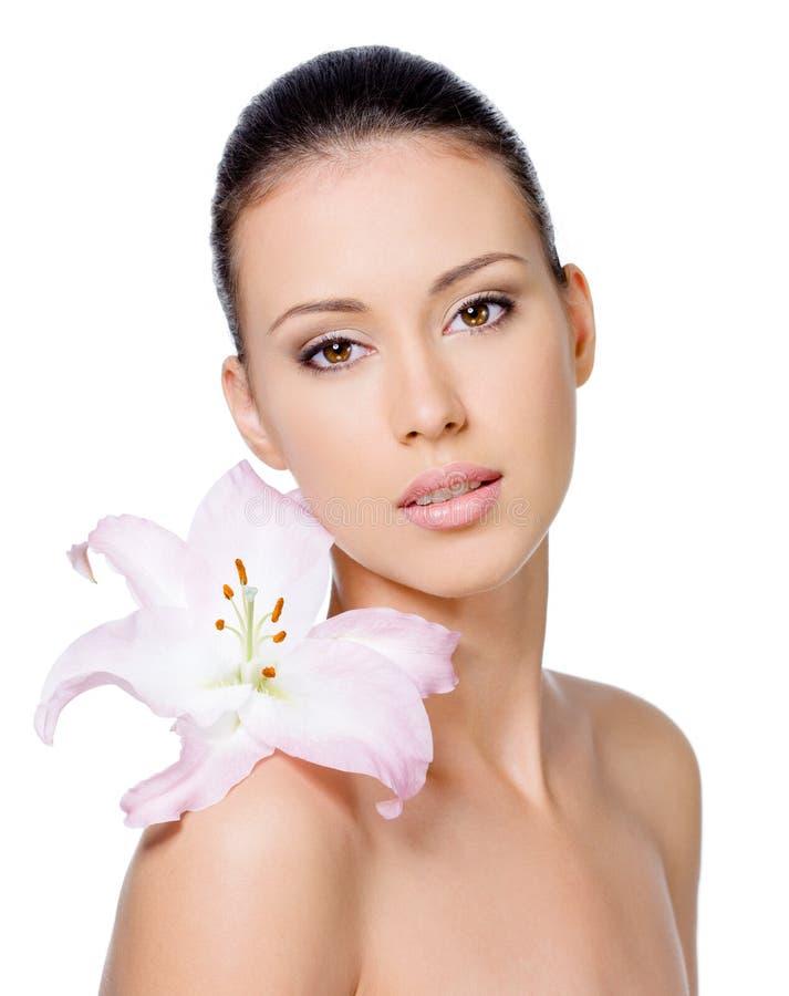 Vrouw met gezonde huid met lelie stock afbeeldingen