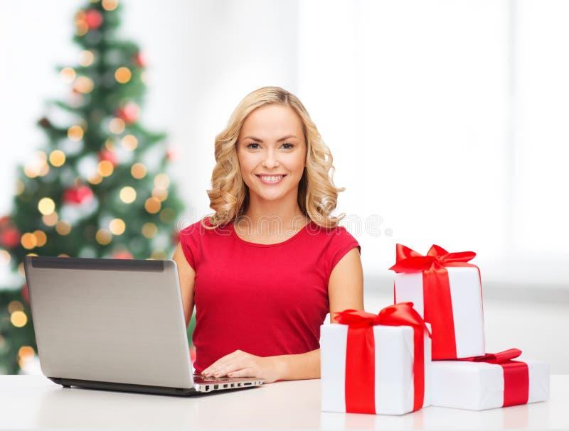 Vrouw met giftdozen en laptop computer royalty-vrije stock afbeeldingen