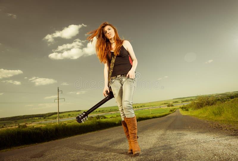 Vrouw met gitaar bij snelweg stock afbeelding