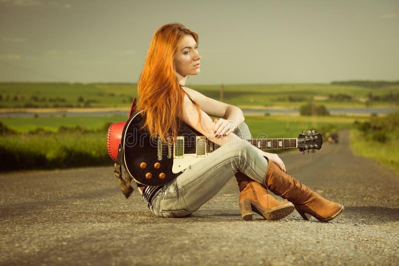Vrouw met gitaarzitting bij asfalt stock fotografie
