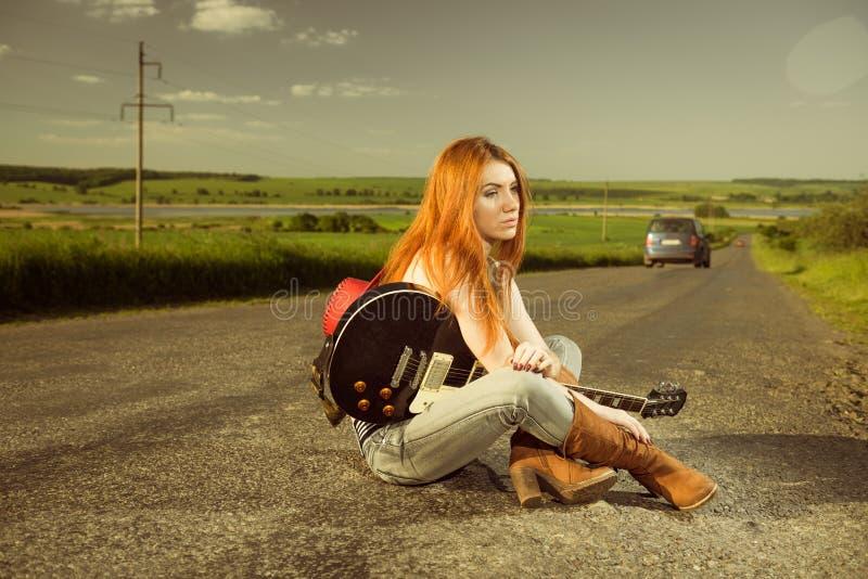Vrouw met gitaarzitting bij asfalt stock afbeeldingen