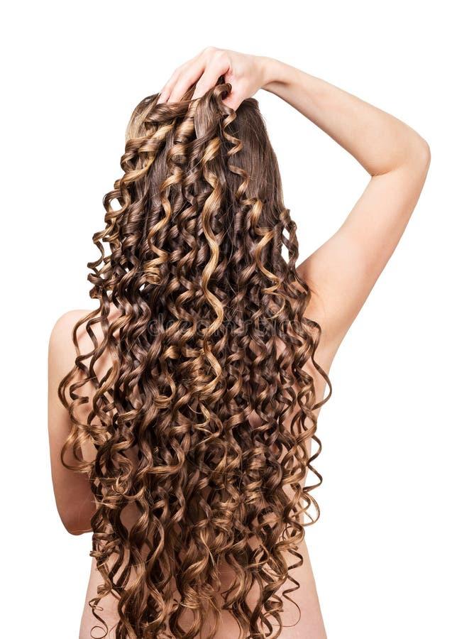 Vrouw met glanzende bruine die krullen op witte achtergrond wordt geïsoleerd stock foto