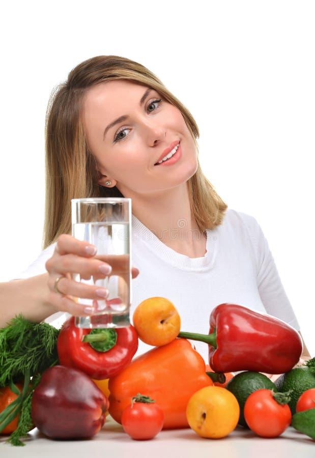 Vrouw met glas zuiver drinkwater en groene groenten en stock afbeelding