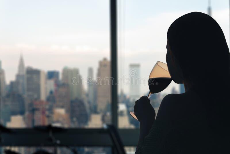 Vrouw met glasse van rode wijn in de flat met de stadsmening van New York royalty-vrije stock afbeelding