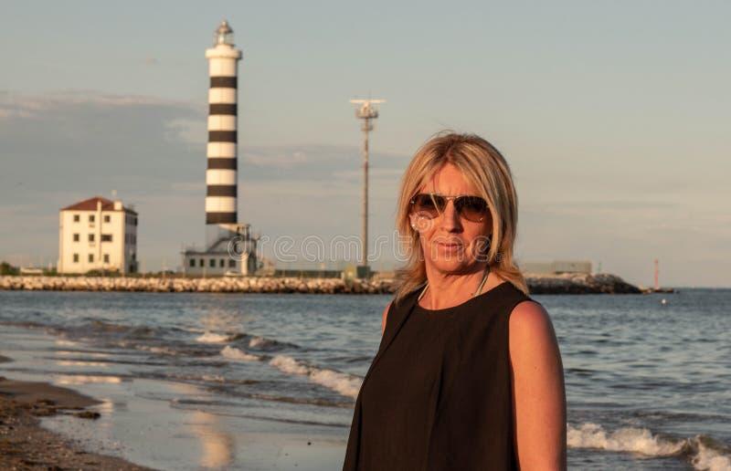 Vrouw met glazen die op het strand met een vuurtoren achter haar voor navigators wordt gefotografeerd foto op de stranden wordt g royalty-vrije stock foto
