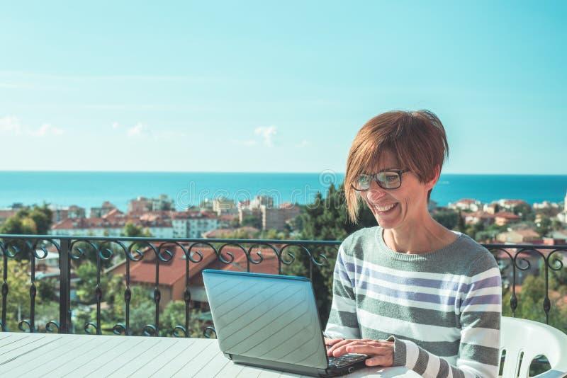 Vrouw met glazen en toevallige kleding die bij laptop in openlucht aan terras werken Mooie achtergrond van groene heuvels en blau royalty-vrije stock afbeeldingen
