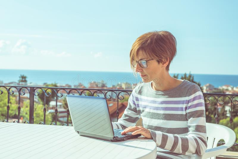 Vrouw met glazen en toevallige kleding die bij laptop in openlucht aan terras werken Mooie achtergrond van groene heuvels en blau stock afbeelding