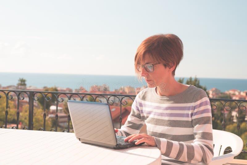 Vrouw met glazen en toevallige kleding die bij laptop in openlucht aan terras werken Mooie achtergrond van groene heuvels en blau stock foto's