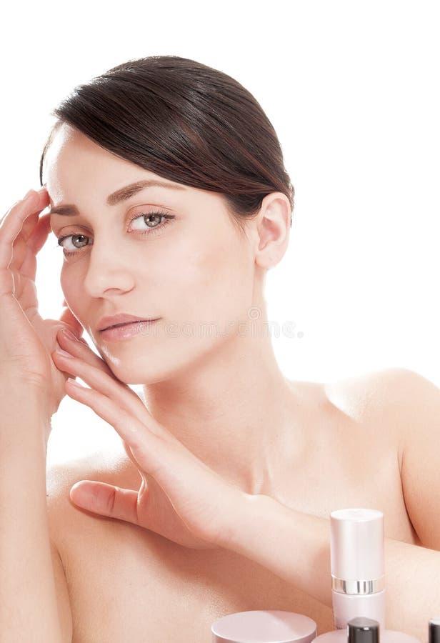 Vrouw met goed-verzorgde huid dichtbij schoonheidsmiddelen. stock afbeeldingen