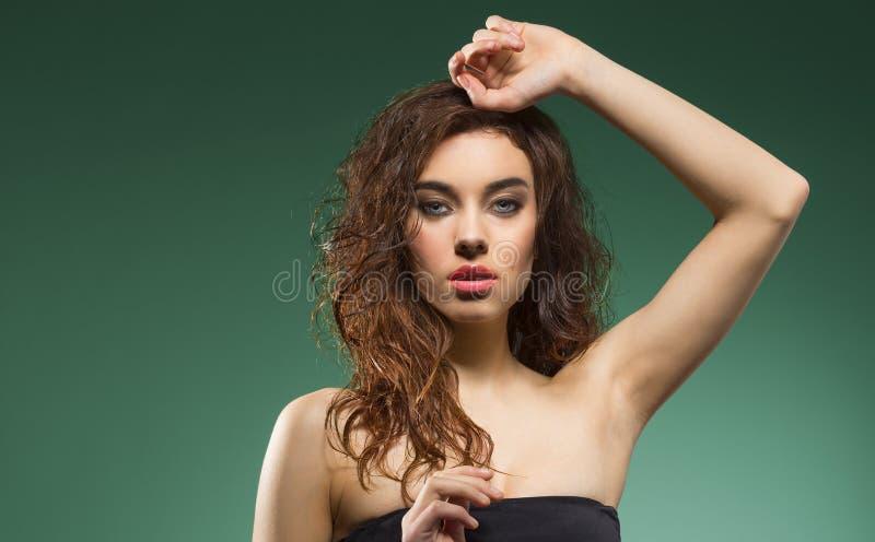 Vrouw met golvend haar op schouder op groen stock foto