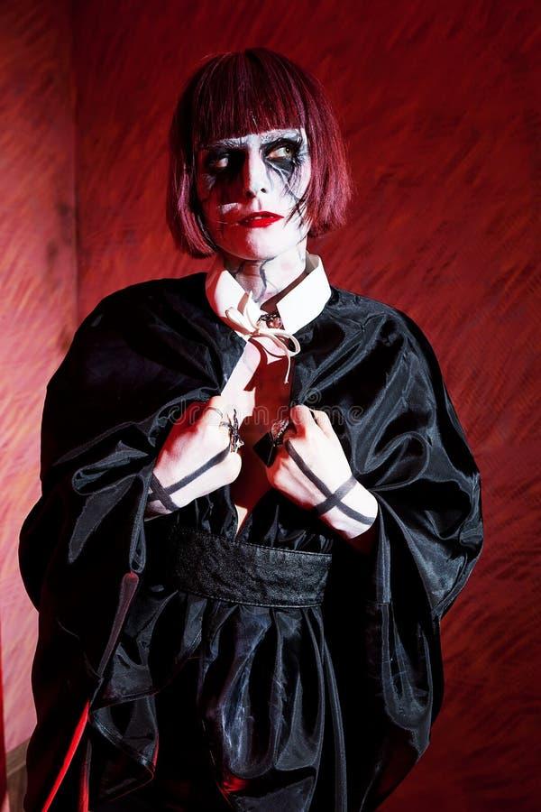 Vrouw met gotische make-up in zwarte mantel met kruisen op hun handen stock afbeelding