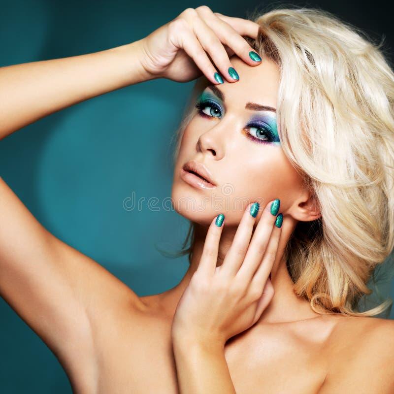 Vrouw met groene spijkers en glamourmake-up van ogen stock afbeelding