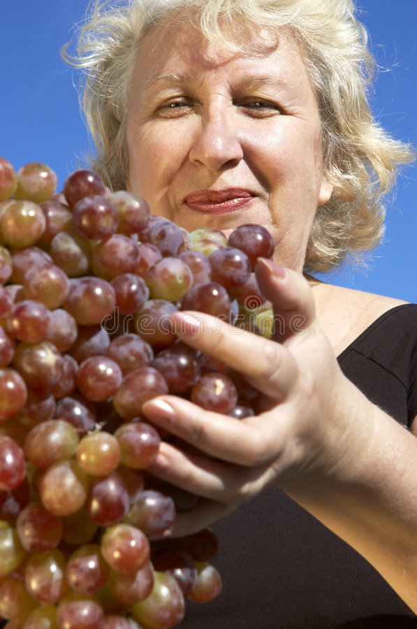 Vrouw met grote druif stock afbeelding