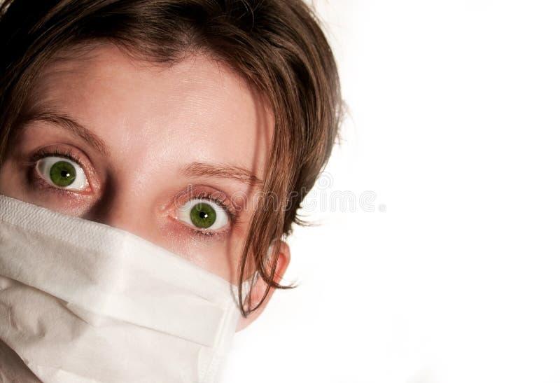 Vrouw met grote groene ogen die medisch masker dragen stock afbeeldingen