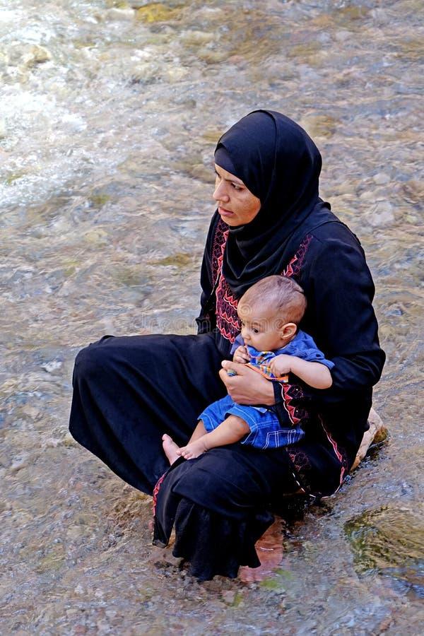 Vrouw met haar baby in de rivier van de Todra-kloven in Marokko stock foto