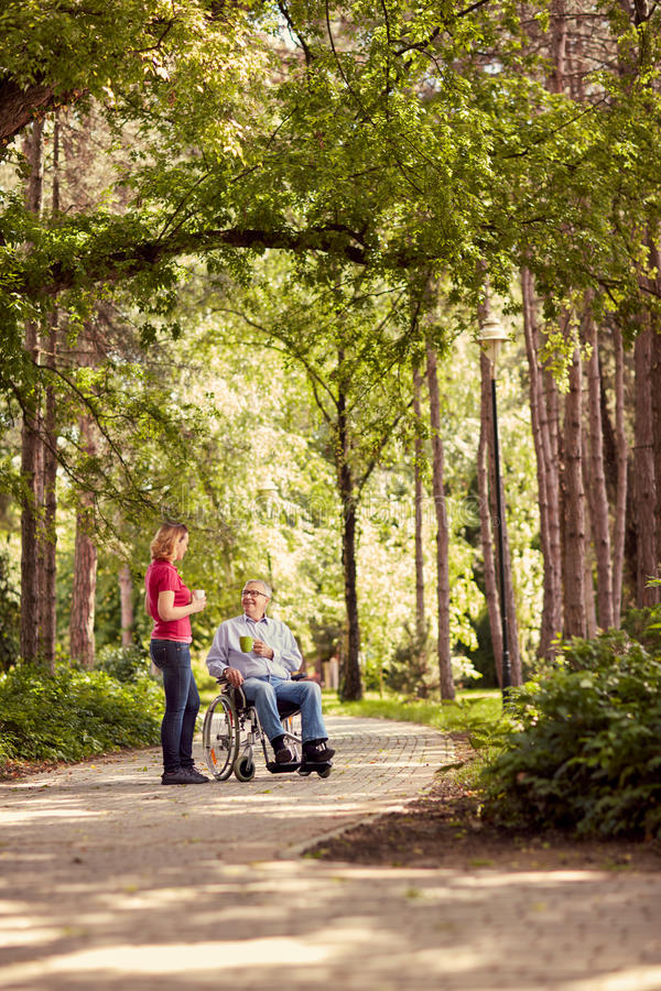 Vrouw met haar gehandicapte gelukkige vader die in rolstoel van tijd genieten royalty-vrije stock foto's