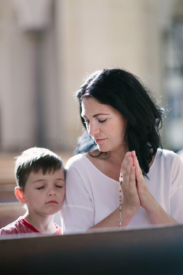 Vrouw met haar zoon het bidden royalty-vrije stock afbeeldingen