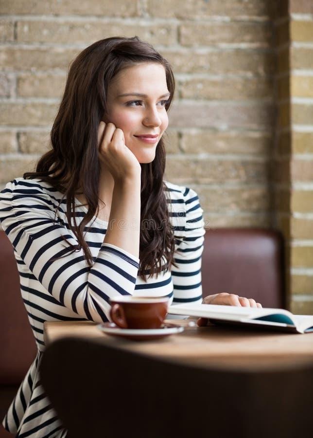 Vrouw met Hand op Chin Looking Away In Coffeeshop royalty-vrije stock foto's