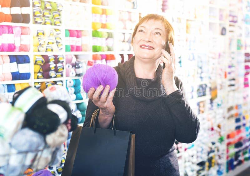 Vrouw met handwerktoebehoren en het spreken op telefoon royalty-vrije stock afbeelding