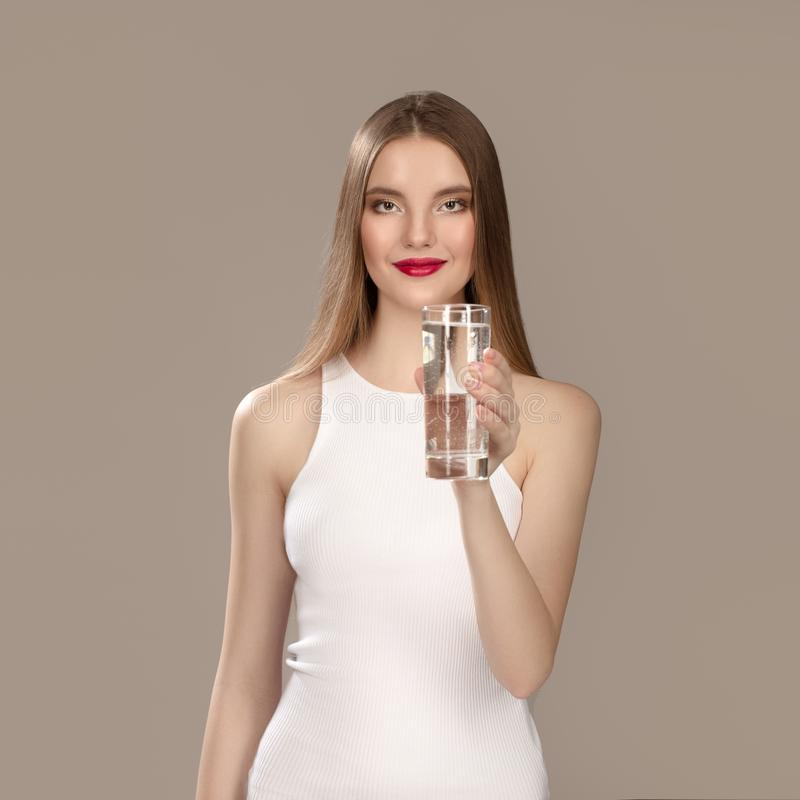 Vrouw met heldere samenstelling in een mooie witte kleding Glimlachend meisjesmineraalwater stock fotografie