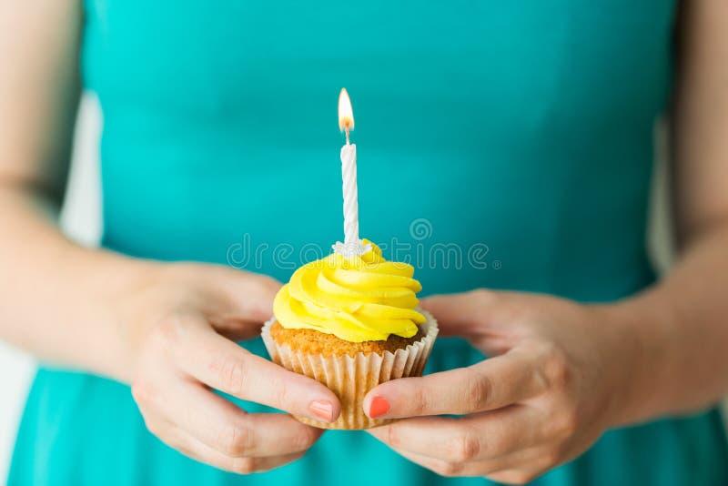 Vrouw met het branden van kaars op verjaardag cupcake royalty-vrije stock foto