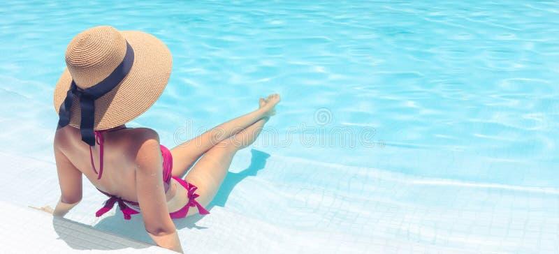 Vrouw met het bruine hoed ontspannen in zwembad met blauw water in zon, vakantieconcept royalty-vrije stock foto