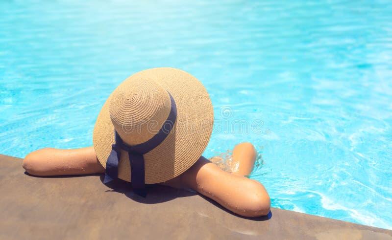 Vrouw met het bruine hoed ontspannen in zwembad met blauw water in zon, vakantieconcept royalty-vrije stock fotografie