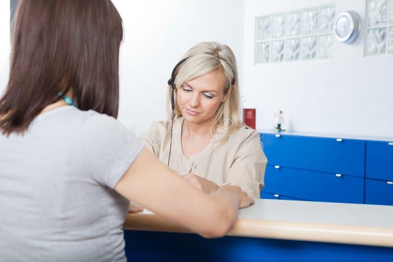 Vrouw met het Bureau van Receptionnistat dentist stock foto