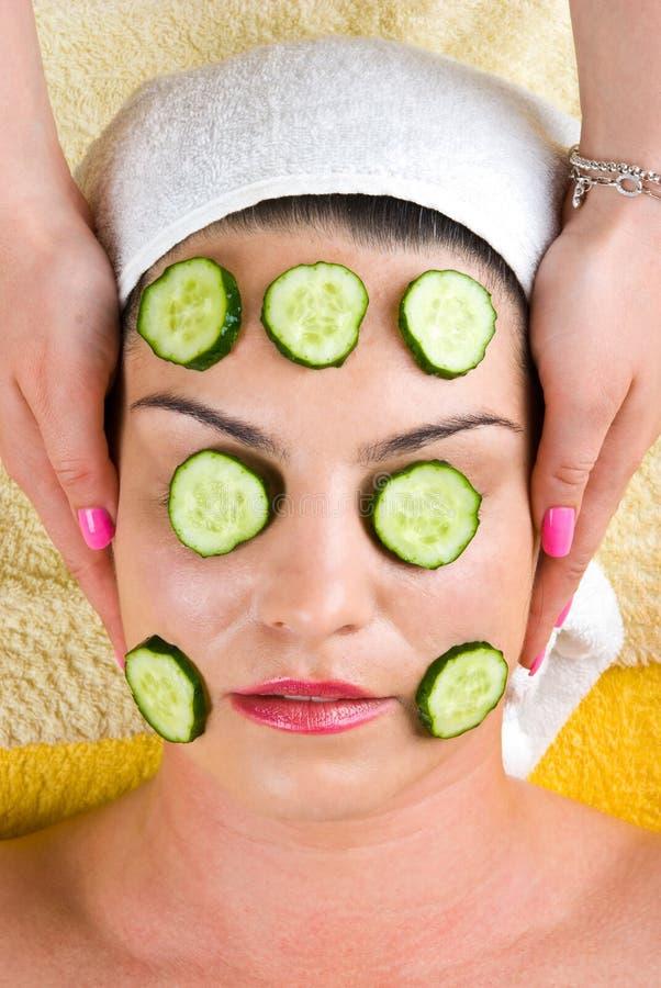 Vrouw met het gezichtsmasker van de komkommerplak bij kuuroord royalty-vrije stock foto's