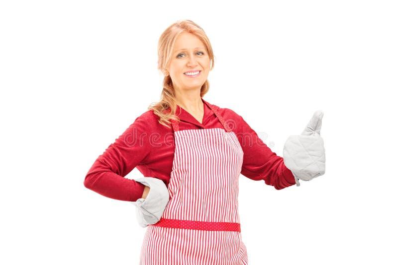 Vrouw met het koken van handschoenen die een duim opgeven stock afbeeldingen