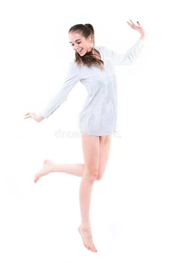 vrouw met het lange benen springen. Geïsoleerdn op witte achtergrond stock fotografie