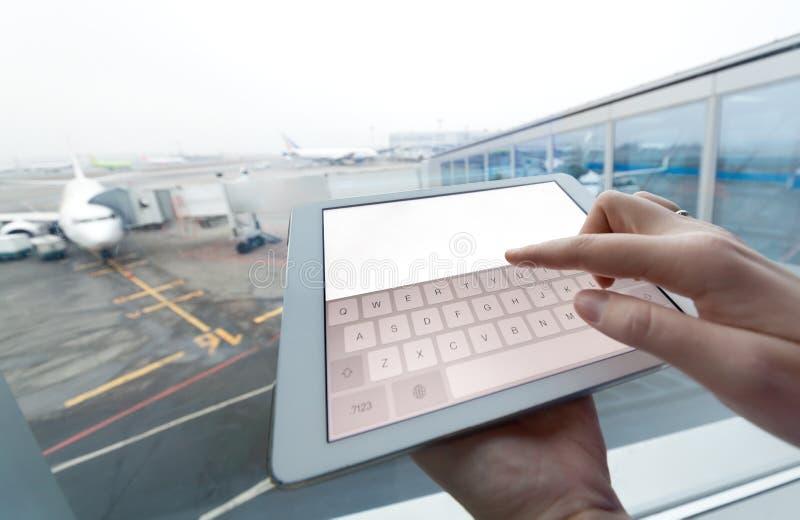 Vrouw met het lege scherm van de tabletcomputer bij luchthaven stock foto's